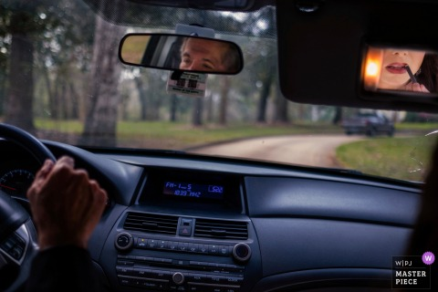 Charleston wedding photographer uses mirrors creatively as we see the groom in the rear view mirror of the car focusing on the dirt road ahead while the bride applies lipstick in the sun visor mirror