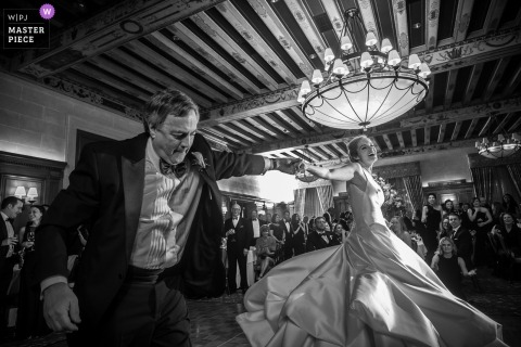 Detroit wedding photographer captured this black and white photograph of a lively father daughter dance under an exposed beam ceiling and large chandelier