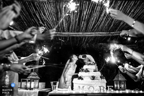 This black and white image of a bride and groom enjoying champagne straight from the bottle as wedding guests hold sparklers in celebration was taken by a Tuscany wedding photographer
