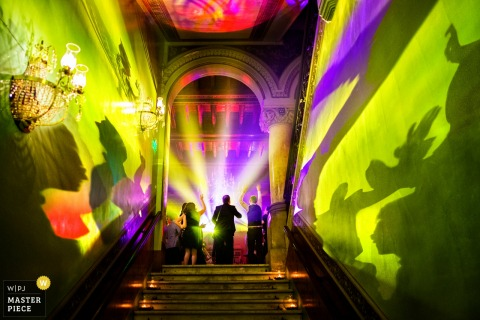 Tuscany wedding photographer created this image of a beautiful staircase being light up by green and purple party lights