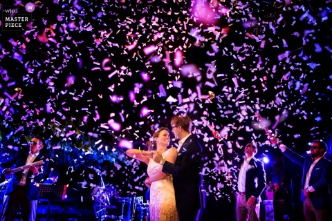 Arezzo wedding photographer captured this image of the bride and groom dancing under a shower of purple confetti under a night sky