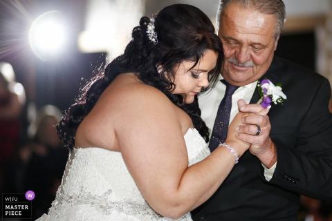 De het huwelijksfotograaf van Madison ving dit beeld van de bruidenvader die haar veel liefs tijdens de dans van de vadendagd bekijken