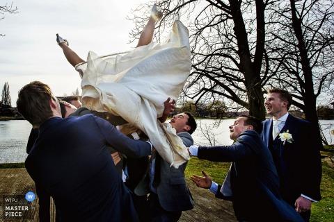 Der niederländische Hochzeitsfotograf schuf dieses alberne Bild einer Braut, die von den Trauzeugen in die Luft geworfen wurde