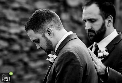 Najlepszy mężczyzna kładzie rękę na ramieniu stajennych, kiedy staje się emocjonalny podczas ceremonii w Winnicach Childress