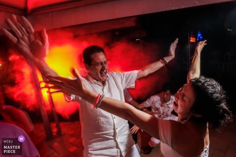 Ibague, Colombia bruid zingt en danst bij de receptie onder rode lichten