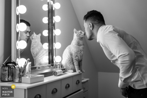 Brive la Gaillarde, France groom kisses his cat while he gets dressed for the wedding