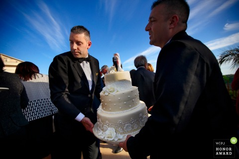 Photo of reception venue staff carrying the wedding cake at the Grand Hotel President, Siderno