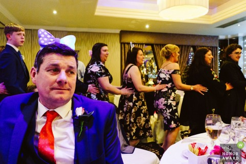 Groom watches on as everyone dances around him at this Cheshire, England reception party