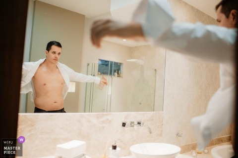 Brazil groom looking at himself in the mirror as he puts a shirt on before the wedding
