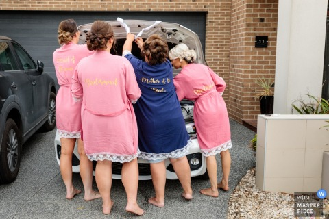 Plumpton, Melbourne, Australia Wedding Photograph of Mother and Bridesmaids working the truck of an auto