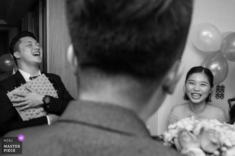 China man of honor and bridesmaid laugh with the groom