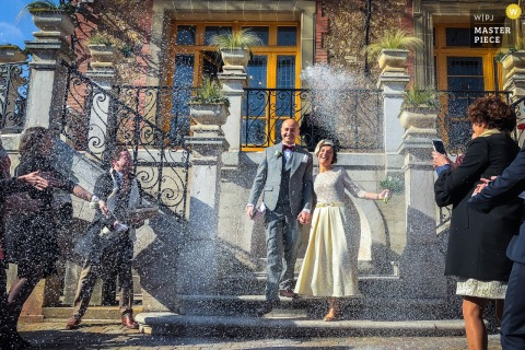 Meudon guests throw rice at the bride and groom outside on a sunny day