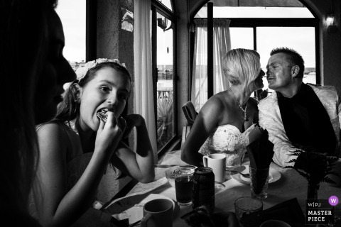 Arguineguin bride and groom about to kiss while girl eats next to them