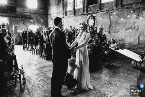 Asylum, London child stands between bride and groom during the ceremony