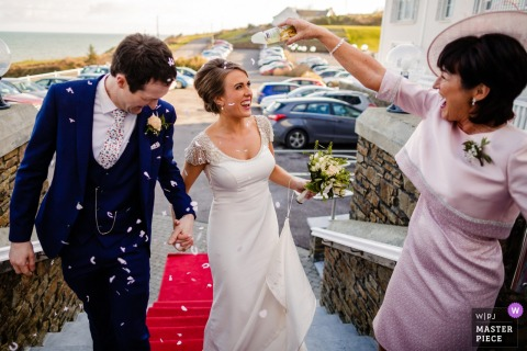 Cork, Ireland guest celebrating with the bride and groom by throwing confetti outside at the wedding