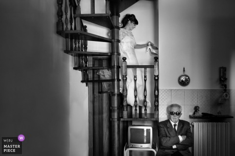 Marche brides father waits as she walks down the stairs before the wedding