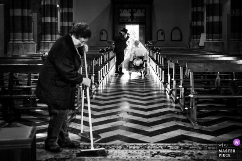 Marche woman sweeps the floor as bride and groom leave the church