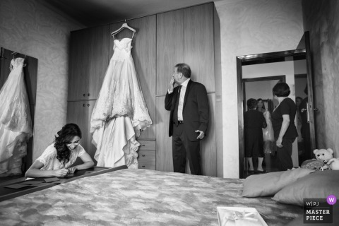 Marche bride has her dress hung up with her father looking at it before the wedding