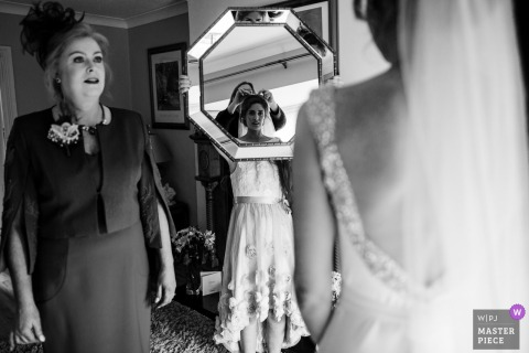 Kildare, Ireland bride looking into the mirror while getting her dress ready before the wedding ceremony