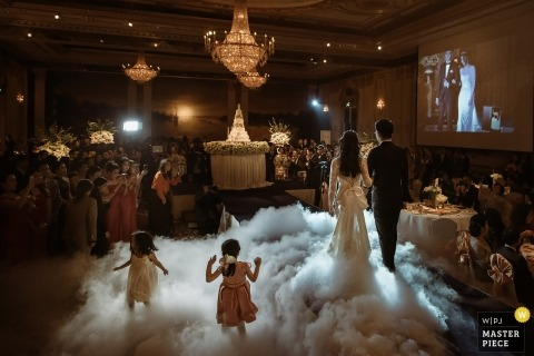 Bangkok, Thailand bride and groom walk in the dance floor fog next to kids at the wedding reception