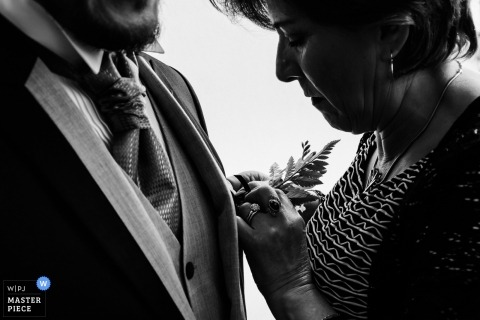 Quito, Ecuador grooms mother helping him get ready with this boutonniere for the wedding