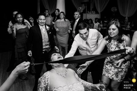 Quito, Ecuador guests and bridal party playing limbo at the wedding reception
