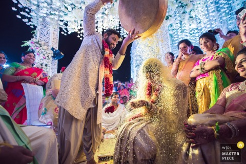 Hyderabad, India groom pours rice onto the bride at the reception under the lights