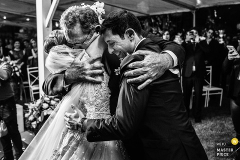 Americana brides father hugs her and the groom at the wedding reception