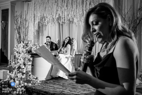 Montreal maid of honor reads her speech at the reception as the bride and groom laugh