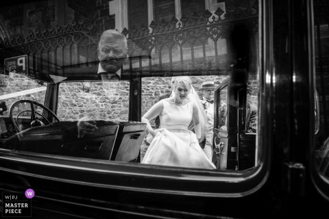 Guernsey bride getting into the vintage wedding car while holding her dress - black-and-white photography