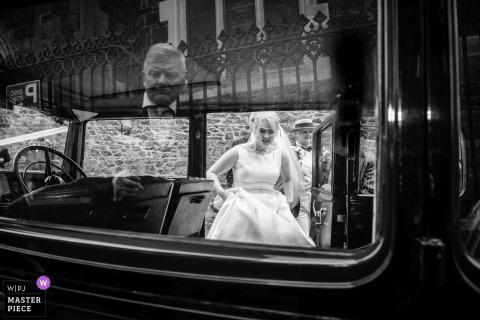 Guernsey-Braut, die in das Weinlesehochzeitsauto beim Halten ihres Kleides - Schwarzweißfotografie kommt