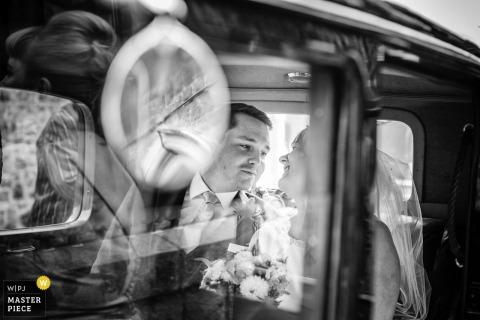 Narzeczeni Guernsey uśmiechają się do siebie w samochodzie po ślubie