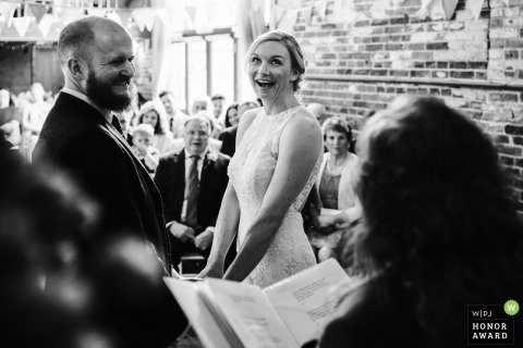 Norfolk, UK wedding reportage photography - bride and groom holding hands and laughing during their vow exchange