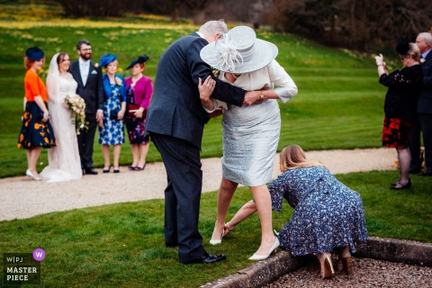 Invités d'Evesham aidant une dame avec sa chaussure pendant que les mariés posent pour une photo en arrière-plan