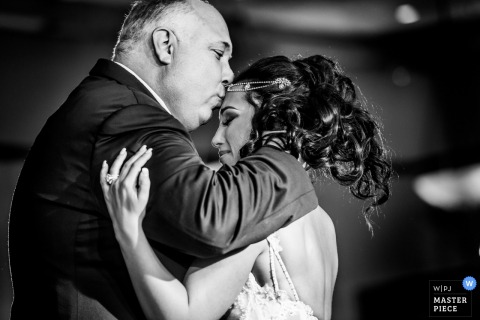 New Jersey brides father kisses her forehead at the reception while they dance