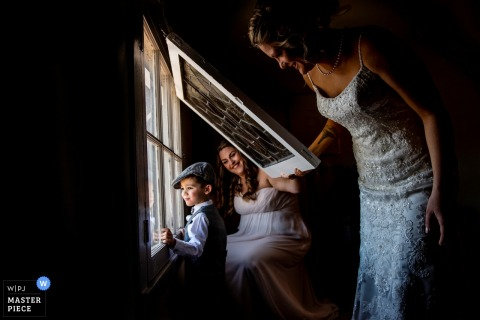 New Jersey boy looks out the window with the bride and maid of honor before the wedding