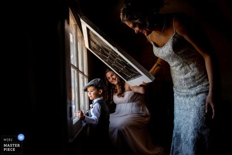Chłopiec z New Jersey wygląda przed oknem z panną młodą i pokojówką przed ślubem