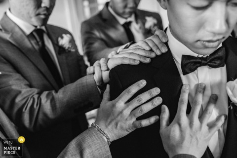 Centreville, Virginia groomsmen put their hands on the groom and pray before the wedding