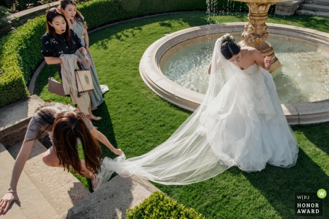 A wedding guest gets her heel stuck in the brides veil by the water fountain at this Los Angeles, California wedding party