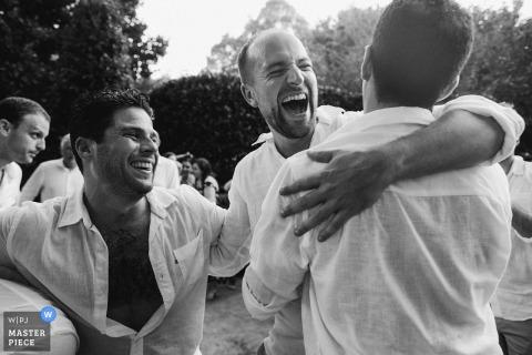 Berry, Australia, los padrinos de boda se ríen y se abrazan en la recepción de la boda