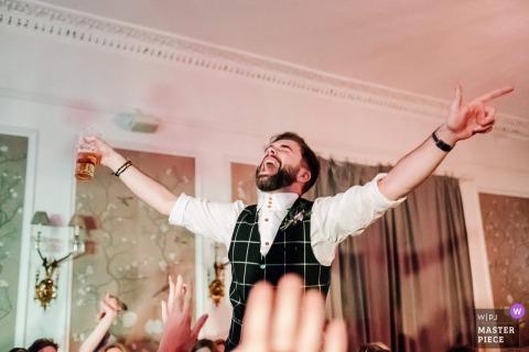 De bruidegom die van Engeland en van dranken drinkt geniet bij de huwelijksontvangst