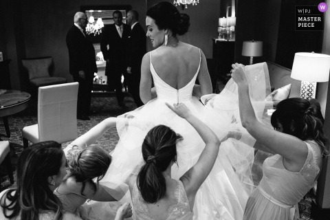 Bride gets help from four bridesmaids with bustling her dress in MN