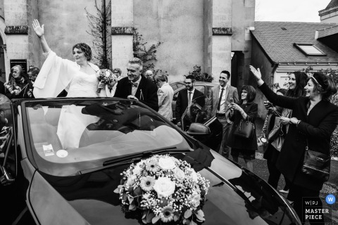 Sainte Gemmes sur Loire bride waving to guests from the back of a convertible car with flowers on the hood