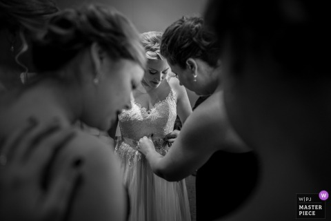 Madison, Wisconsin bridesmaid helping the bride with her dress