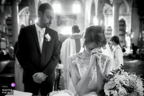 Bride prays while groom watches at the wedding ceremony