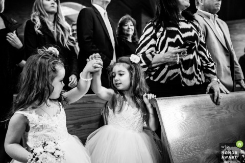 New Jersey flower girls hold hands during the church ceremony