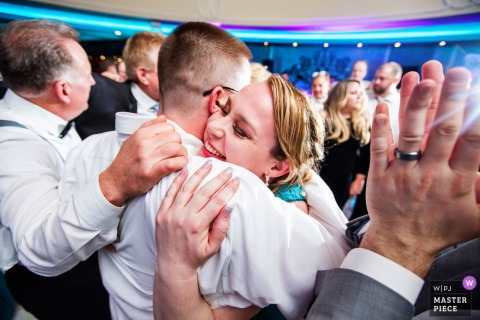 New Jersey bride hugs a guest at the wedding reception