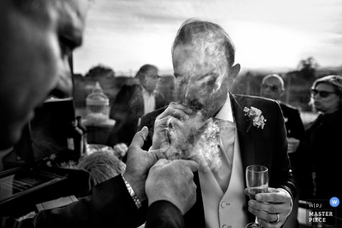 Calabria groom smoking a cigar at the wedding reception