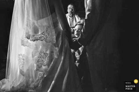 Brazil boy looks at the bride in her dress in amazement during the ceremony
