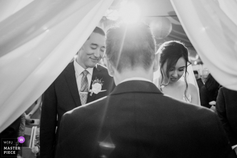 Bride and groom smile during the ceremony at Laguna beach, California